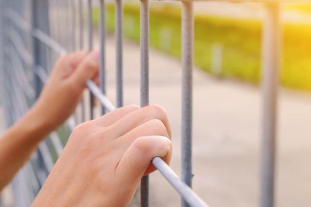 The womens hand is on the iron grate waiting for liberation. Stock Photo