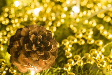 Soft focused on Pine cones surrounded by gold bead and Christmas party accessories on wooden table Stock Photo