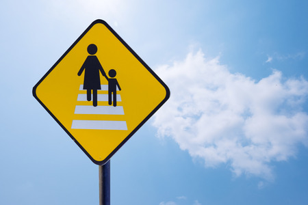 Caution people crossing traffic sign isolated on blue sky background with clipping path included.