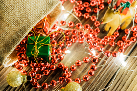 Gift box overflowing from brown sacks. There are festive lights around, red beads and reindeer are all placed on the old wood floor with deep grooves.