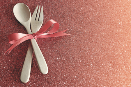 Wooden spoons and forks are strapped together with a bright red ribbon placed on a red gliiter background,dinner for lover in valentines day. Reklamní fotografie