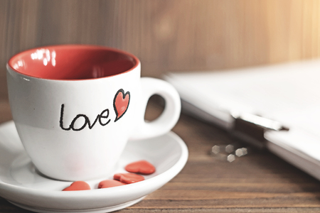 White cup with Love letter at side  on wooden background