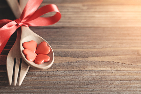 Wooden spoons and forks are strapped together with a bright red ribbon,red heart in wooden spoon placed on a wooden background