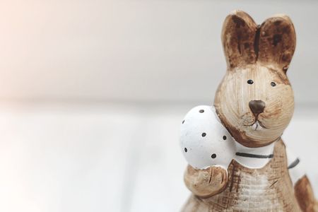 Rabbit is holding an white Easter egg, standing on a white wooden floor. Meaning  celebrate Easter seasonal. Festival of the beginning And rebirth Stock Photo