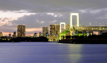 Rainbow bridge on Sunset at Odaiba beach at Tokyo , Japan