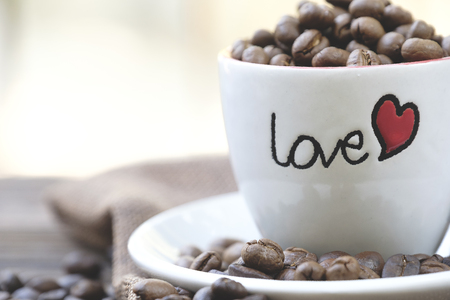 Roasted coffee bean in Love cup on wodden table surrounded by coffee bean Stockfoto