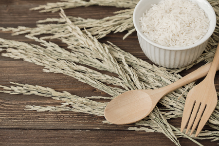 Wooden spoon and fork with yellow rice plant on white wooden background.
