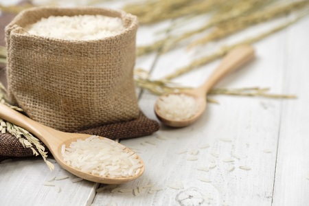 A wooden spoon filled with rice placed on wooden background.