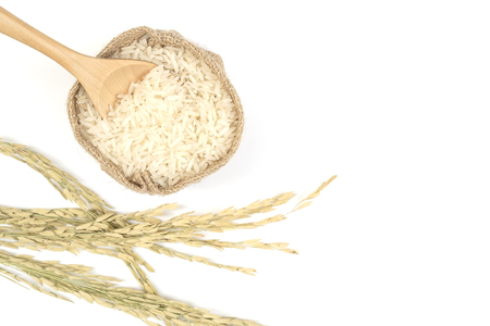 Rice in sack and wooden spoon on white background