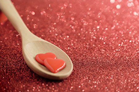 Little two heart in wooden spoon on glitter red background.