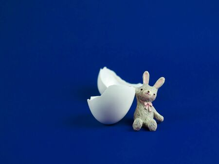 Cute rabbit doll with egg shell broken crack on blue background, Easter concept