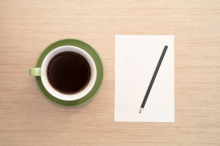 A green cup of coffee on the background of a table and a white sheet of paper simulates the beginning and pencil Banco de Imagens