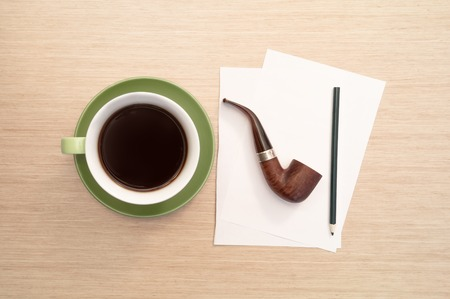 A green cup of coffee on the background of a table and a white blank sheet of paper, a pencil and a smoking pipe simulates thought and thoughtfulness. Banco de Imagens