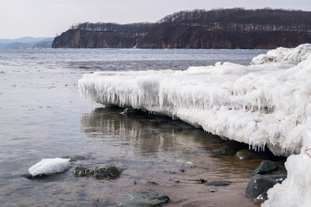 The snow-covered icy beach in the sunny warm last winter day awaits the arrival of spring. Melts ice and snow