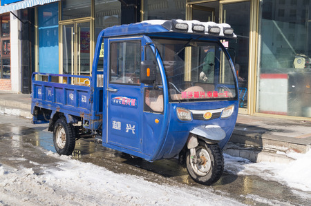 Hunchun, Jilin, China - March 8, 2018: Three-wheel motor scooter with a cab is traditionally used for cargo delivery services or passengers throughout the territory of China and other countries Editorial