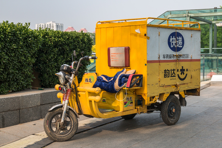 a three-wheel scooter or motobike with a cab on the streets next to the Olympic Park in Beijing Editorial