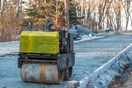 Manual compact asphalt roller for tamping soil at a construction site in a public park.