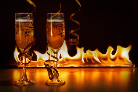 Two glasses of sparkling champagne with golden ribbons against the bokeh background of bright flames creating a cozy atmosphere of Christmas or New Year Stock Photo