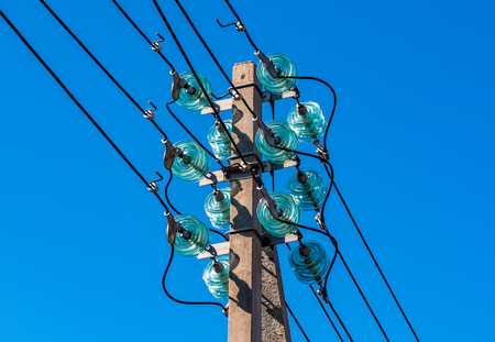 Concrete pole with electrical wires and high-voltage distribution insulators as part of a transmission line against a blue sky.