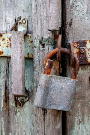 The staple of the broken lock is sawn and hinged on the old wooden door