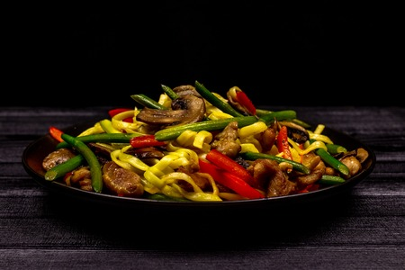 Appetizing stir fried noodles with garlic sprouts, mushrooms, red pepper and chicken meat on a black rustic background of a wooden table. A popular Asian dish.