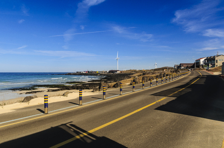 Beautiful view Woljeong Beach besides trunk road providing leading line at Jeju Island South Korea with white windmill at far left backed by awesome blue sky background
