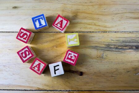 Conceptual of stay safe and sanitized during pandemic, danger and uncertainties. Wooden alphabet cubes forming words STAY SAFE in oval shape over wooden table. Focus of selective cubes.