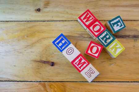 Conceptual of work from home during lockdown directives during virus outbreak. Wooden alphabet cubes forming WORK FROM HOME. Focus on selective cubes only. Stock Photo