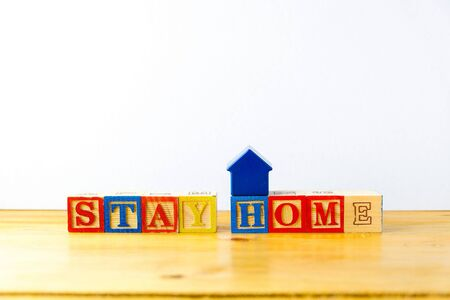 Conceptual of stay at home during movement control order to stop the chain of virus outbreak. Wooden alphabet cubes forming words STAY HOME. Focus on selective cubes. Stock Photo