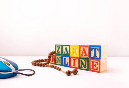 Wooden blocks, mouse and beads on white. Conceptual of zakat online (alms-giving) payment during covid-19 lockdown as annual obligation to aid the poor muslim community. Selective focus.