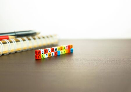 Conceptual of accumulated depreciation in financial statements. Colorful alphabet beads stacked forming the words over dark table. Spiral notebook and pencil visible. Focus on text on beads at front. Archivio Fotografico