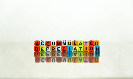 Conceptual of accumulated depreciation in financial statements. Colorful alphabet beads stacked forming the words over dark table. Selective Focus.