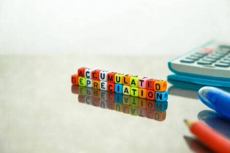 Conceptual of accumulated depreciation in financial statements. Colorful alphabet beads stacked forming the words over dark table. Spiral notebook and pencil visible. Focus on text on beads at front. Stock fotó