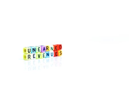 Conceptual of unearned revenues in financial statements. Colorful alphabet beads isolated over reflective white surface. Focus of text R at center. Others in gradient blur.