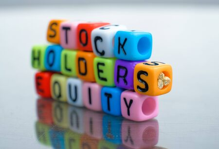 Conceptual of stockholders equity as balance sheet items  spelled on alphabet beads. Isolated over reflective dark background. Focus on beads at center; other in gradient blur