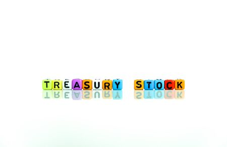 onceptual of treasury stock in financial statements. Colorful alphabet beads isolated over reflective white surface. Focus of text on beads STOCK on right. Others in gradient blur.