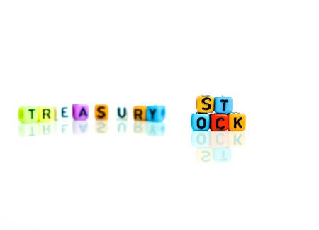 Conceptual of treasury stock in financial statements. Colorful alphabet beads isolated over reflective white surface. Focus of text on beads at center. Others in gradient blur.