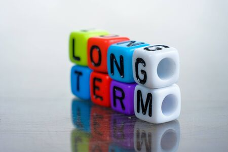 Conceptual of long term balance sheet items in financial statements spelled on alphabet beads. Isolated over reflective dark background. Focus on alphabet G on white bead; other in blur