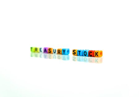 Conceptual of treasury stock in financial statements. Colorful alphabet beads isolated over reflective white surface. Focus of text on beads STOCK on right. Others in gradient blur. Archivio Fotografico