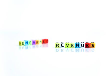 onceptual of unearned revenues in financial statements. Colorful alphabet beads isolated over reflective white surface. Focus of text R at center. Others in gradient blur.
