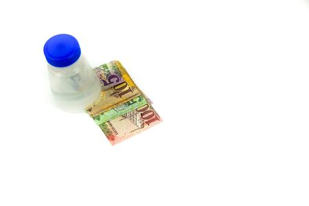 Isolated image of saudi riyal bank notes in SAR5, 10, 50 and 100 denomination underneath plastic bottle over white. Focus on denomination texts on SAR 100 notes . Stock Photo