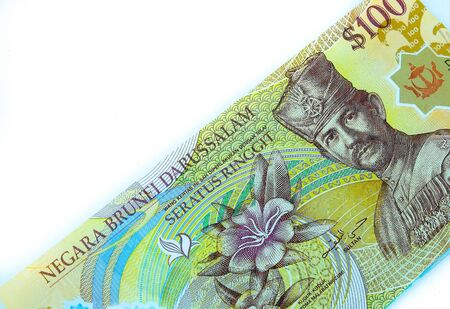 Image of colourful $100 brunei dollar banknotes over white. Focus on banknotes.