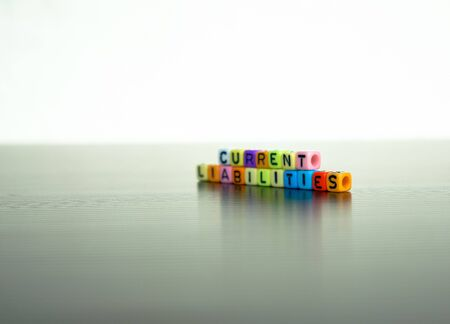 Conceptual of current liabilities of financial statements. Colorful stacked alphabet beads over reflective grey surface. Focus on beads at center.