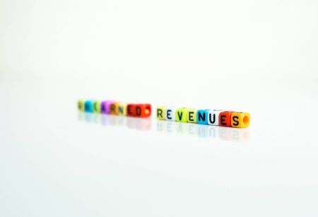 Conceptual of unearned revenues in financial statements. Colorful alphabet beads isolated over reflective white surface. Focus on beads closer to foreground. Others in gradient blur.