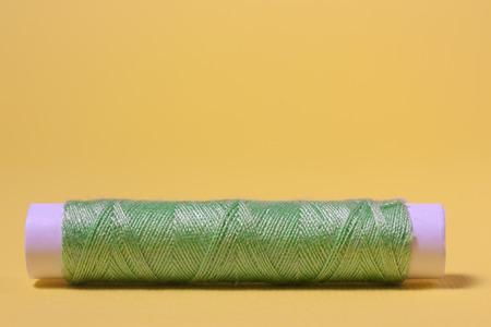 cotton thread: Green cotton thread on a yellow background
