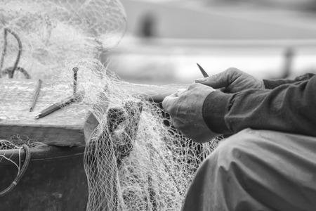 Mains d'un pêcheur, il nettoie son filet de pêche
