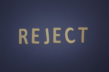 Reject written with wooden letters on a blue background to mean a business concept