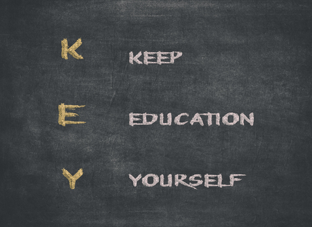 KEY acronym - KEEP EDUCATING YOURSELF. Educational concept with different color sticky notes and white chalk handwriting on a blackboard to mean a concept