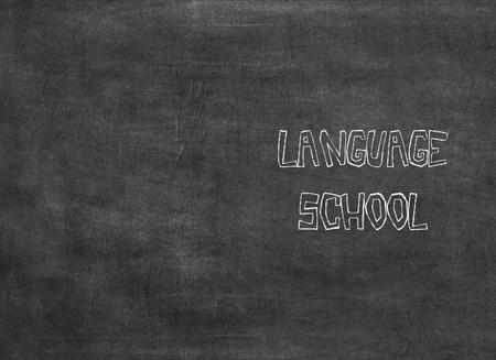 Language School written in chalk on an old blackboard to mean a concept