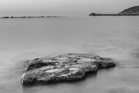 Black and white. Long exposure of the beach and rocks of an Italian coast Фото со стока